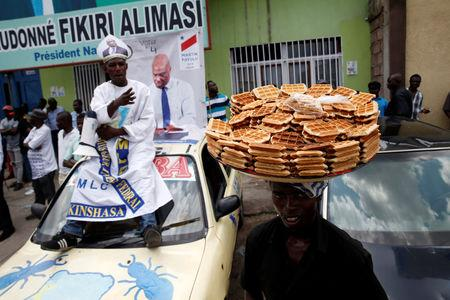 A vender sells waffle near supporters of the runner-up in Democratic Republic of Congo's presidential election, Martin Fayulu before a political rally in Kinshasa, Democratic Republic of Congo, January 11, 2019. REUTERS/Baz Ratner