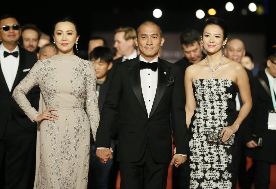 """Hong Kong actor Tony Leung, middle, poses with his wife Carina Lau, left and Chinese actress Zhang Ziyi arrive at the 50th Golden Horse Awards in Taipei, Taiwan, Saturday, Nov. 23, 2013. Leung is nominated as Best Leading Actor for the film """" The Grandmaster"""" at this year's Golden Horse Awards -one of the Chinese-language film industry's biggest annual events. (AP Photo/Wally Santana)"""
