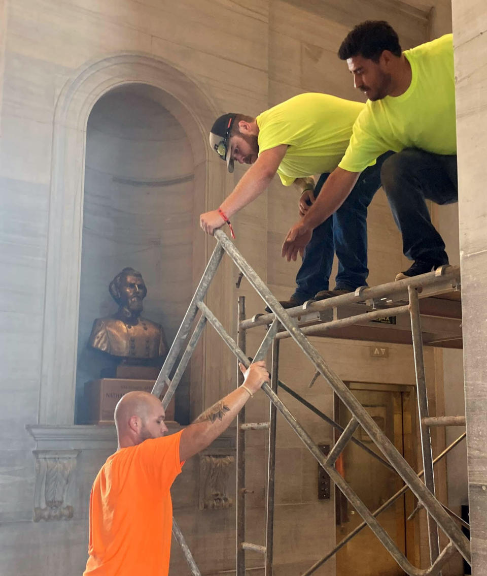 Workers prepare scaffolding in front of a bust of Confederate general and early Ku Klux Klan leader Nathan Bedford Forrest at the State Capitol, Thursday, July 22, 2021, in Nashville, Tenn. A decades-long effort to remove the bust from the Tennessee Capitol cleared its final hurdle Thursday, with state leaders approving the final vote needed to allow the statue to be relocated to a museum. (AP Photo/Kimberlee Kruesi)