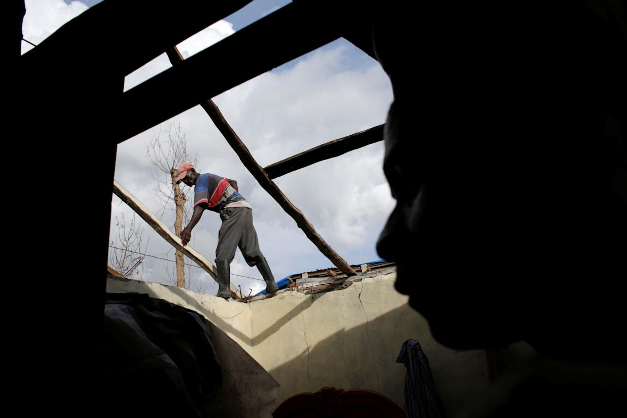 A boy looks at a man as he rebuildsthe roof ofa house affected by Hurricane Matthew in Damassinson Oct. 22, 2016.