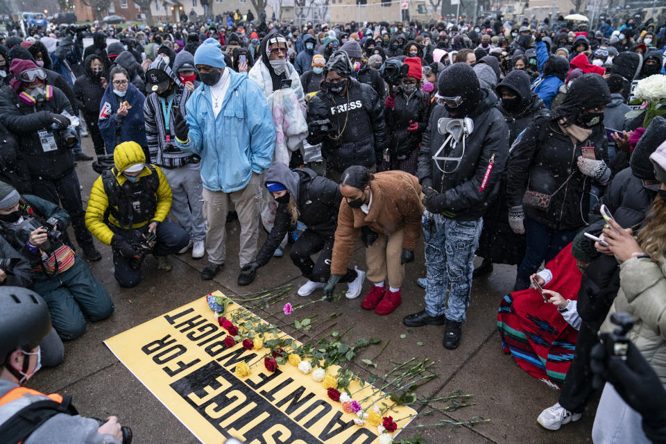 Flowers are placed on a banner as demonstrators gather outside the Brooklyn Center Police Department on Tuesday, April 13, 2021, to protest the shooting death of Daunte Wright on Sunday during a traffic stop in Brooklyn Center, Minn. (AP Photo/John Minchillo)