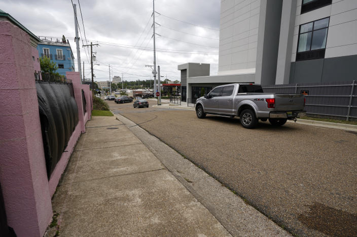 """Traffic moves past the Jackson Women's Health Organization clinic, also known as """"The Pink House,"""" on the left and a upscale motel on the right, Wednesday, May 19, 2021, in Jackson, Miss. The clinic's fencing is shrouded with a black tarp so that its clients may enter in privacy, while the motel has put up privacy fencing. The Supreme Court agreed to take up a dispute over a Mississippi ban on abortions after 15 weeks of pregnancy, with their decision affecting whether the state's only medical facility will continue to be able to provide abortions on demand. (AP Photo/Rogelio V. Solis)"""