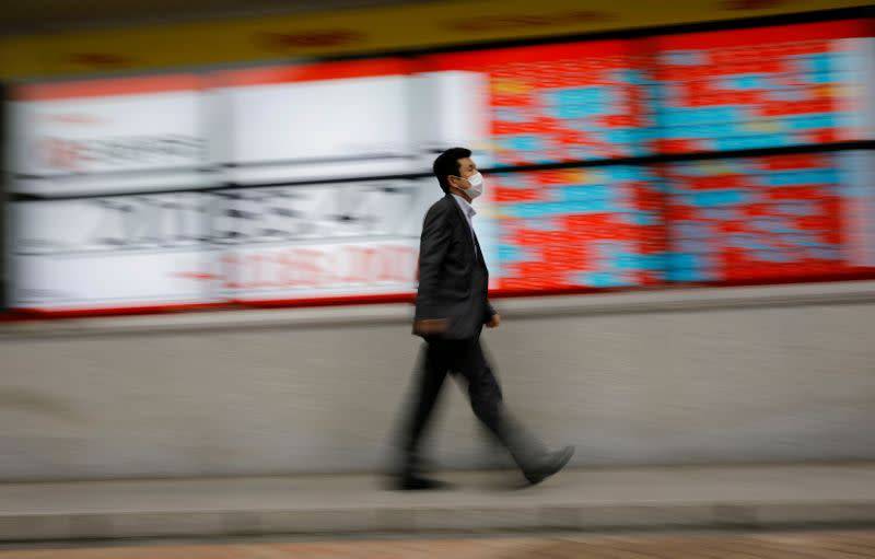 FILE PHOTO: A man wearing a protective face mask, following the coronavirus disease (COVID-19) outbreak, walks in front of a stock quotation board outside a brokerage in Tokyo