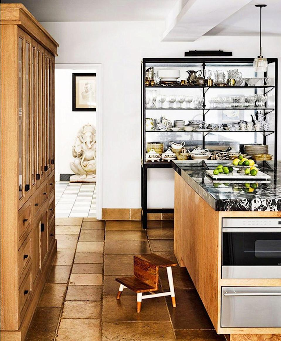 <p>Use open shelving to add to the utilitarian feel that's still stylish. In this kitchen, Romanek Design Studio opted for a shelving unit that didn't require any renovations and complements the formal black marble surfaces as well as the more casual tile floors. </p>