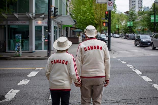 A couple hold hands while waiting to cross a street in Vancouver, British Columbia on Tuesday. (Ben Nelms/CBC - image credit)