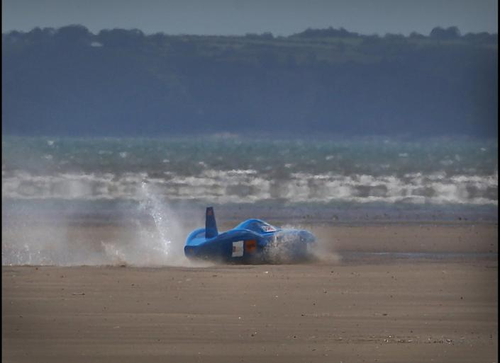 Driver Joe Wales crashes through the surf after veering off course during an attempt on the British land speed record for battery-powered vehicles in the Bluebird Electric on Pendine Sands on August 14, 2011 in Pendine, Wales. Driver Joe Wales and his father, fellow driver Don Wales, come from a famous family who have been setting land and water speed records since 1924. Don holds the current UK record of 137 miles an hour in an electric vehicle.