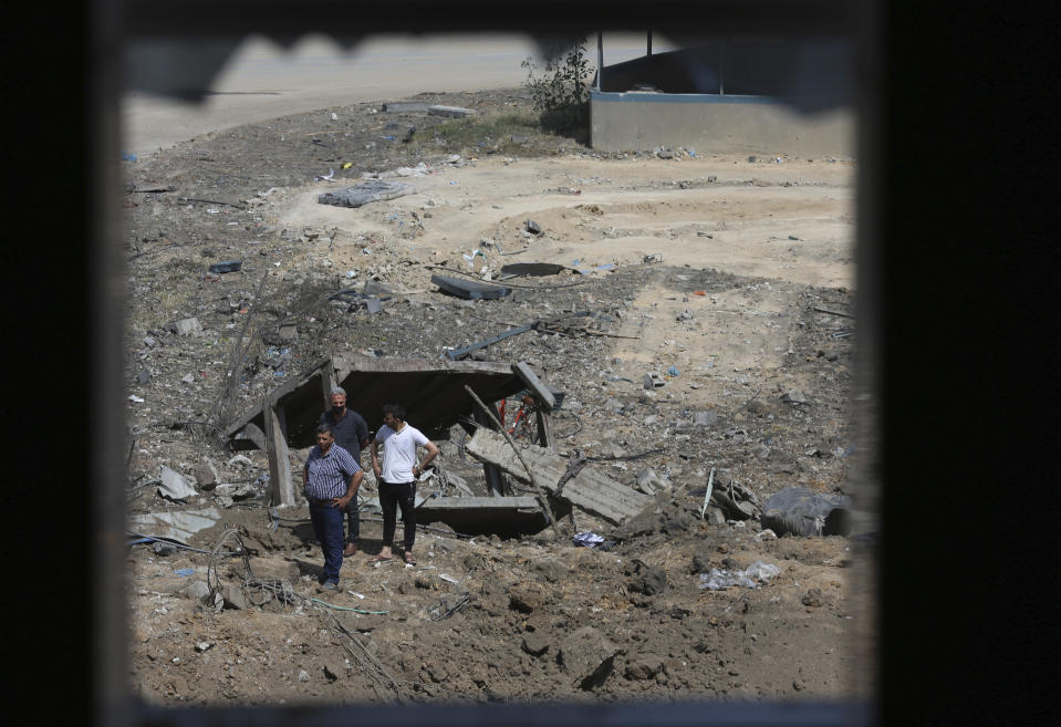 Palestinians inspect the rubble of an ice factory and mechanics garages destroyed by an Israeli airstrikes, in Gaza City, Tuesday, May 11, 2021. (AP Photo/Adel Hana)