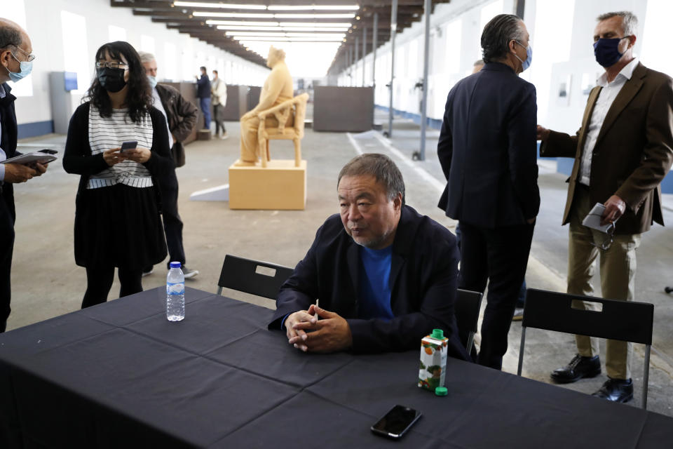 """Dissident Chinese artist Ai Weiwei sits at a table at the end of a news conference during a press preview of his new exhibition """"Rapture"""" in Lisbon, Thursday, June 3, 2021. The world-renowned artist is putting on the biggest show of his career, and he is doing it in a place he's fallen in love with: Portugal. (AP Photo/Armando Franca)"""