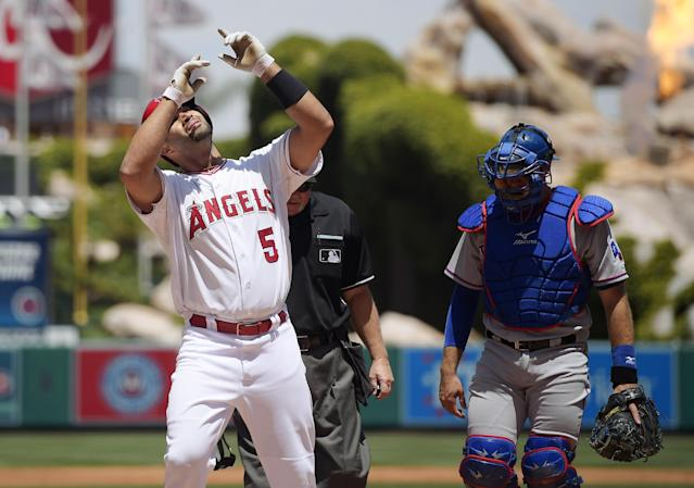 Los Angeles Angels' Albert Pujols, left, points to the sky after as Texas Rangers catcher J.P. Arencibia looks on after hitting a solo home run during the first inning of a baseball game, Sunday, May 4, 2014, in Anaheim, Calif. (AP Photo/Mark J. Terrill)