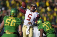 Florida State quarterback Jameis Winston, center, looks to pass under pressure by Oregon defensive lineman Alex Balducci, left, and Tyson Coleman during the first half of the Rose Bowl NCAA college football playoff semifinal, Thursday, Jan. 1, 2015, in Pasadena, Calif. (AP Photo/Mark J. Terrill)