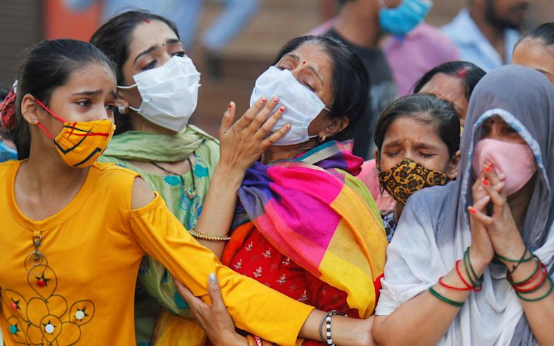 Relatives mourn the death of a man due to the coronavirus at a crematorium in New Delhi - Reuters