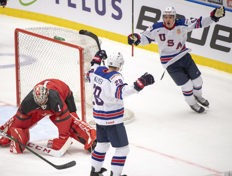 The United States' Arthur Kaliyev (28) celebrates his goal with teammate Trevor Zegras, right, as Canada goaltender Nick Daws looks on during first period at the World Junior Hockey Championships in Ostrava, Czech Republic, Thursday, Dec. 26, 2019. (Ryan Remiorz/The Canadian Press via AP)