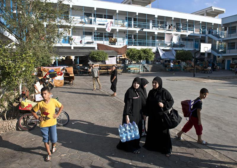 Palestinian women displaced from their homes when fighting broke out between Israel and Hamas militants stand in the courtyard of a United Nations school in Jabalia, after receiving water bottles and food aid on August 16, 2014 (AFP Photo/Roberto Schmidt)