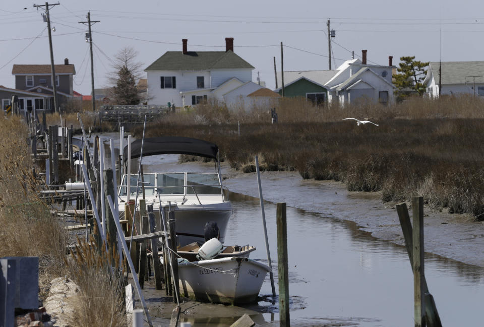 FIL - This Wednesday April 3, 2013 file photo shows a creek along with boats on Tangier Island, Va. The fishing community in the middle of the Chesapeake Bay has reported zero cases of the coronavirus. But the virus would be devastating if it were to reach the island, which has a large elderly population and no full-time doctor. (AP Photo/Steve Helber)