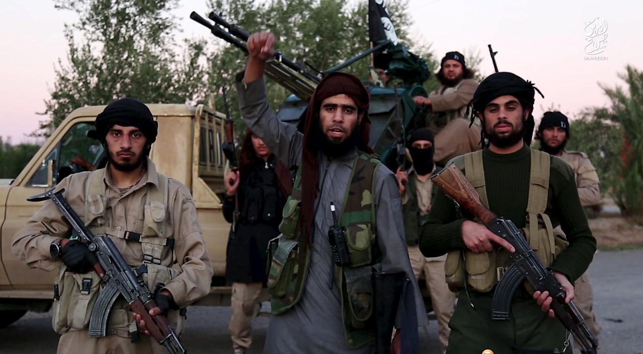 A man (C) identified in the subtitiles as Al Karar the Iraqi gestures as he speaks at an undisclosed location in this image taken from undated video footage released by Islamic State. Islamic State warned in the new video on November 16, 2015 that countries taking part in air strikes against Syria would suffer the same fate as France, and threatened to attack in Washington. The video, which appeared on a site used by Islamic State to post its messages, begins with news footage of the aftermath of Friday's Paris shootings in which at least 129 people were killed. REUTERS/Social Media Website via Reuters TVATTENTION EDITORS - THIS PICTURE WAS PROVIDED BY A THIRD PARTY. REUTERS IS UNABLE TO INDEPENDENTLY VERIFY THE AUTHENTICITY, CONTENT, LOCATION OR DATE OF THIS IMAGE. THIS PICTURE IS DISTRIBUTED EXACTLY AS RECEIVED BY REUTERS, AS A SERVICE TO CLIENTS. FOR EDITORIAL USE ONLY. NOT FOR SALE FOR MARKETING OR ADVERTISING CAMPAIGNS. NO RESALES. NO ARCHIVE.      TPX IMAGES OF THE DAY