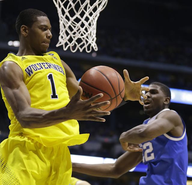 Michigan's Glenn Robinson III (1) grabs a rebound in front of Kentucky's Alex Poythress (22) during the first half of an NCAA Midwest Regional final college basketball tournament game Sunday, March 30, 2014, in Indianapolis. (AP Photo/Michael Conroy)