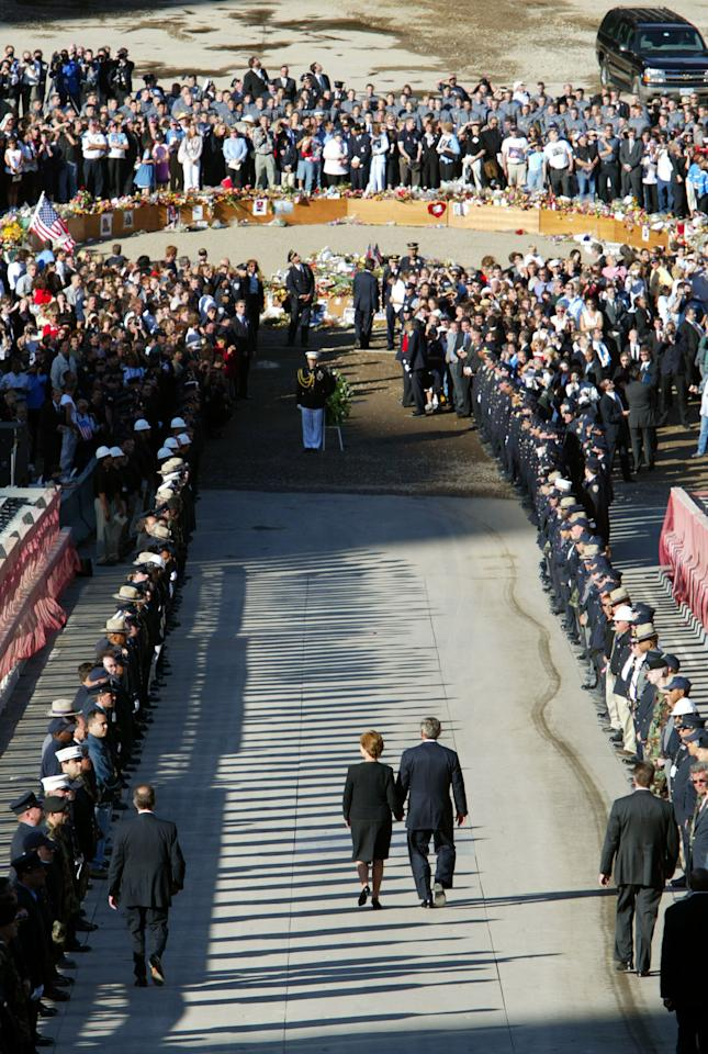 "U.S. President George W. Bush and first lady Laura Bush walk past an honor guard as they proceed down the ramp into the pit at the site of the World Trade Center in New York September 11, 2002. Bush is visiting all three disaster sites in Washington, Pennsylvania and Washington on the one year anniversary of the attacks, and cautioned Americans that the United States has ""determined enemies"" and that the country is ""not invulnerable to their attacks."" (REUTERS/Shaun Best GMH/GN)"