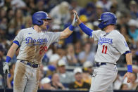 Los Angeles Dodgers' AJ Pollock (11) is greeted by Billy McKinney after scoring from third off a sacrifice fly by Cody Bellinger during the fourth inning of the team's baseball game against the San Diego Padres, Thursday, Aug. 26, 2021, in San Diego. (AP Photo/Gregory Bull)
