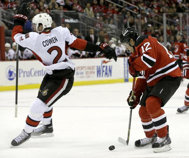 Ottawa Senators defenseman Jared Cowen (2) loses his stick while New Jersey Devils ring wing Damien Brunner (12), of the Czech Republic, steals the puck moments before scoring a goal during the second period of an NHL hockey game, Wednesday, Dec. 18, 2013, in Newark, N.J. (AP Photo/Julio Cortez)
