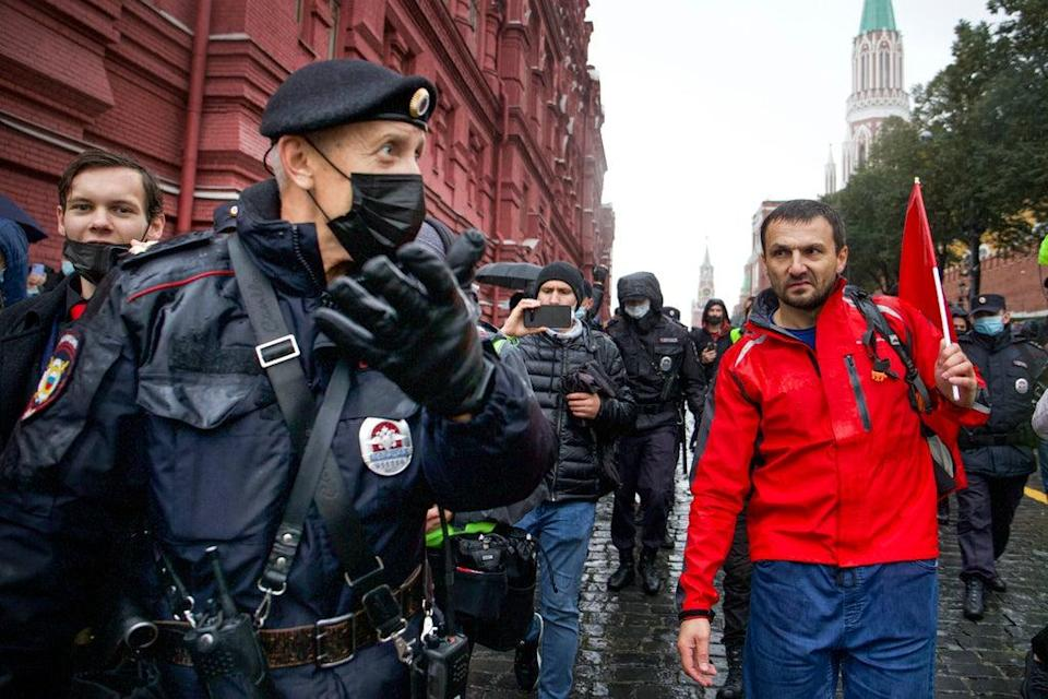 Police escort a demonstrator near Red Square in Moscow during Saturday's muted protest against election fraud (AP)