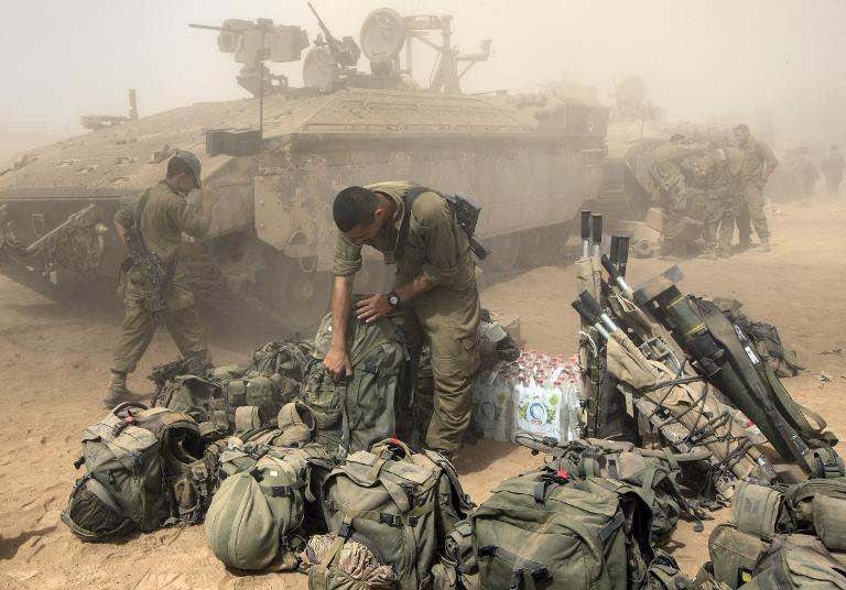 An Israeli soldier prepares his equipment at an army deployment area, on the southern Israeli border with the Gaza Strip, on August 1, 2014