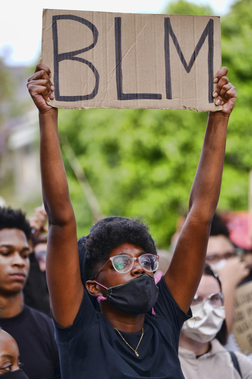 Pictured is a Black Lives Matter protester holding up a sign with the letters BLM.