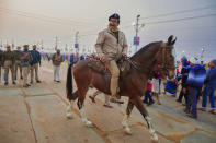 Inspector General of Police Kavinder Pratap Singh patrols on horseback during Magh Mela festival, in Prayagraj, India. Tuesday, Feb. 16, 2021. Millions of people have joined a 45-day long Hindu bathing festival in this northern Indian city, where devotees take a holy dip at Sangam, the sacred confluence of the rivers Ganga, Yamuna and the mythical Saraswati. Here, they bathe on certain days considered to be auspicious in the belief that they be cleansed of all sins. (AP Photo/Rajesh Kumar Singh)