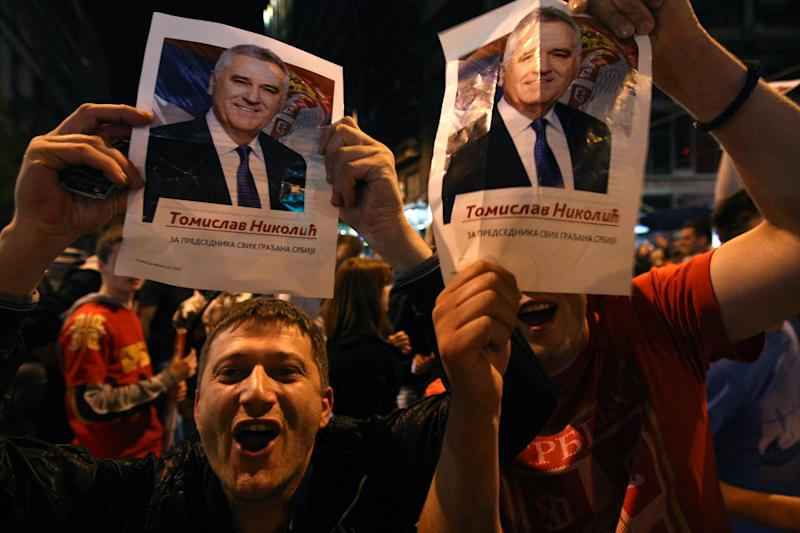 Supporters of Serbian Progressive Party leader Tomislav Nikolic with his pictures celebrate after presidential elections in downtown Belgrade, Serbia, Sunday, May 20, 2012. Nationalist Tomislav Nikolic beat pro European Union incumbent Boris Tadic in Serbia's presidential runoff election. (AP Photo)