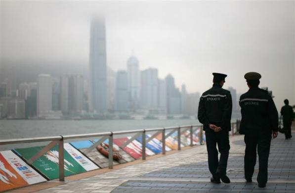 Two policemen patrol the Avenue of Stars, along the Victoria Harbour waterfront in Tsim Sha Tsui, Hong Kong on a misty day December 15, 2009.