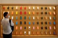 FILE PHOTO: A man stands in front of a wall of iPhones cases in Beijing
