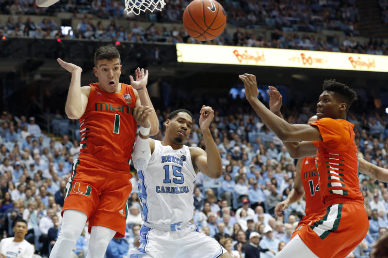North Carolina forward Garrison Brooks, center, struggles for a rebound with Miami guard Dejan Vasiljevic, left, and forward Anthony Walker, right, during the first half of an NCAA college basketball game in Chapel Hill, N.C., Saturday, Jan. 25, 2020. (AP Photo/Gerry Broome)