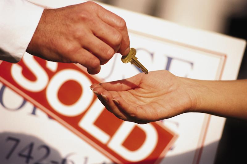 Man's hand giving a home key to another person with a