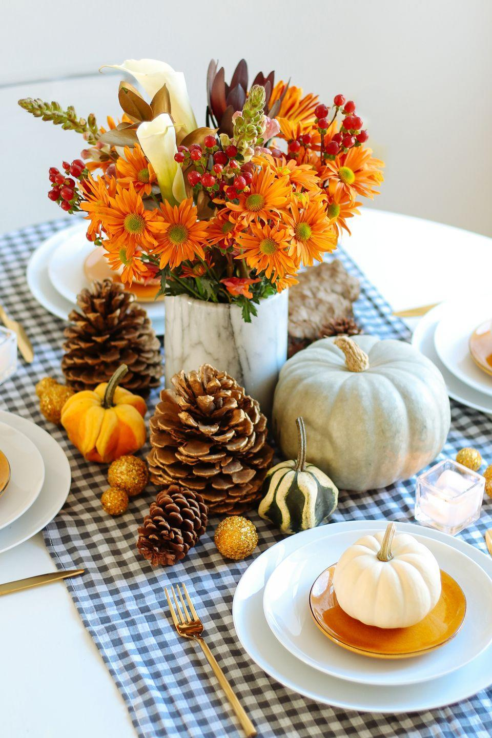 """<p>Add some simple country charm to your Thanksgiving table with a blue and white gingham table runner accessorized with pinecones, white pumpkins, gourds, and the Julia centerpiece, $40, by <a href=""""https://go.redirectingat.com?id=74968X1596630&url=https%3A%2F%2Furbanstems.com%2F&sref=https%3A%2F%2Fwww.countryliving.com%2Fentertaining%2Fg2130%2Fthanksgiving-centerpieces%2F"""" rel=""""nofollow noopener"""" target=""""_blank"""" data-ylk=""""slk:UrbanStems"""" class=""""link rapid-noclick-resp"""">UrbanStems</a>. </p><p><a class=""""link rapid-noclick-resp"""" href=""""https://www.amazon.com/artificial-flowers/b?ie=UTF8&node=14087331&tag=syn-yahoo-20&ascsubtag=%5Bartid%7C10050.g.2130%5Bsrc%7Cyahoo-us"""" rel=""""nofollow noopener"""" target=""""_blank"""" data-ylk=""""slk:SHOP FAUX FLOWERS"""">SHOP FAUX FLOWERS</a></p>"""
