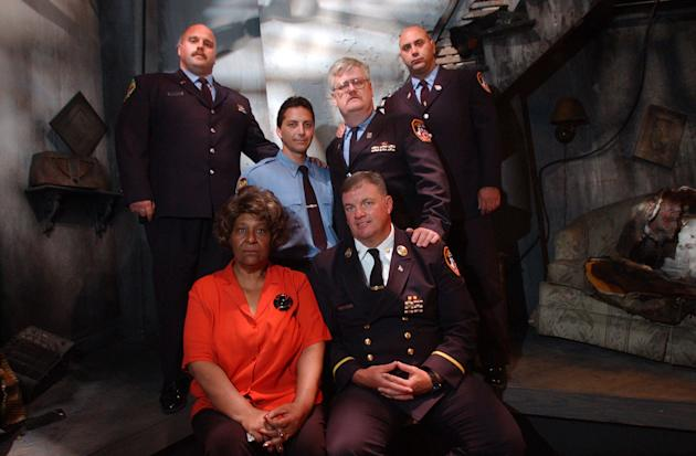 Firefighters Bill Butler, left, Matt Komorowski, Captain Jay Jonas, seated, Mike Meldrum and Sal D'Agostino were reunited with Ms. Harris at the FDNY's Fire Safety Learning Center in 2002. (The Providence Journal / John Freidah)