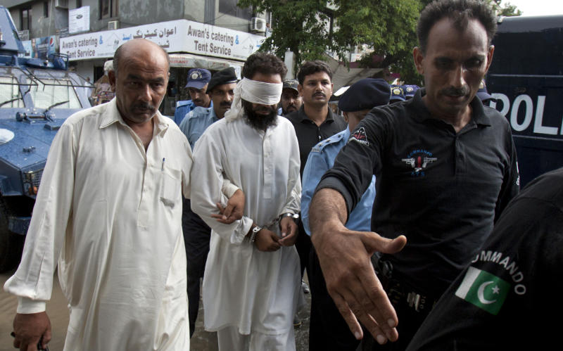 Pakistani police officers escort blindfolded Muslim cleric Khalid Chishti to court in Islamabad, Pakistan, Sunday, Sept. 2, 2012. In the latest twist in a religiously charged case that has focused attention on the country's harsh blasphemy laws, Pakistani police arrested Chishti who they say planted evidence in the case of a Christian girl accused of blasphemy. (AP Photo/Anjum Naveed)