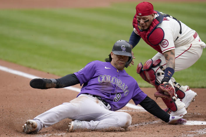Colorado Rockies' Connor Joe (9) slides after being tagged out at home by St. Louis Cardinals catcher Yadier Molina during the second inning of a baseball game Saturday, May 8, 2021, in St. Louis. (AP Photo/Jeff Roberson)
