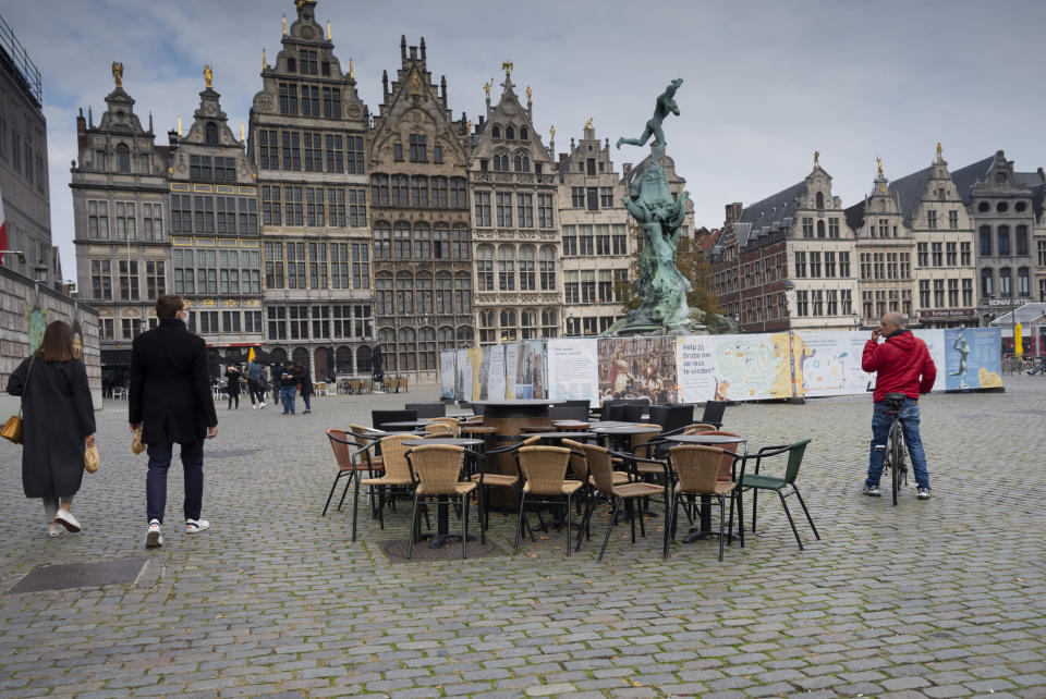 People walk by chairs and tables of an empty terrace in the historical center of Antwerp, Belgium, Sunday, Oct. 18, 2020. Faced with a resurgence of coronavirus cases, the Belgian government on Friday announced new restrictions to try to hold the disease in check, including a night-time curfew and the closure of cafes, bars and restaurants for a month. The measures will take effect on Monday, Oct. 19, 2020. (AP Photo/Virginia Mayo)