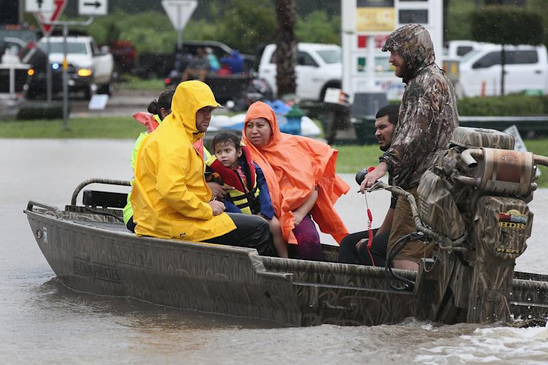 Rescue workers and volunteers help residents make their way out of a flooded neighborhood after it was inundated with rain water following Hurricane Harvey on Aug. 29 in Houston.  (Scott Olson/Getty Images)