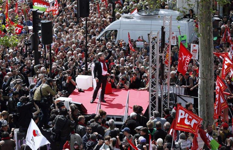 Jean-Luc Melenchon (C), leader of Front de Gauche (Left Front) left wing party raises his fist as he gives a speech on stage on May 5, 2013 in Paris, during a demonstration