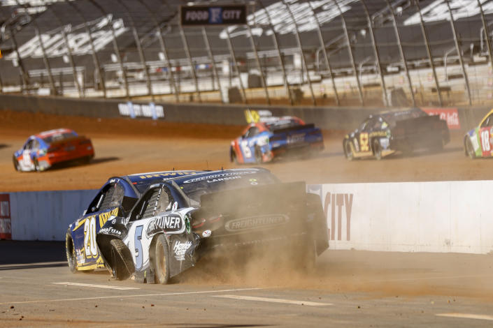 Driver Kyle Larson (5) pushes Christopher Bell (20) down pit road after a wreck during a NASCAR Cup Series auto race, Monday, March 29, 2021, in Bristol, Tenn. (AP Photo/Wade Payne)