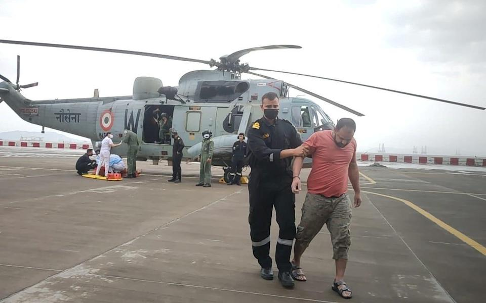 A member of the Indian Navy helps a man to walk after he was rescued by Indian Navy personnel from a sunken barge in the Arabian Sea after cyclone Tauktae's landfall