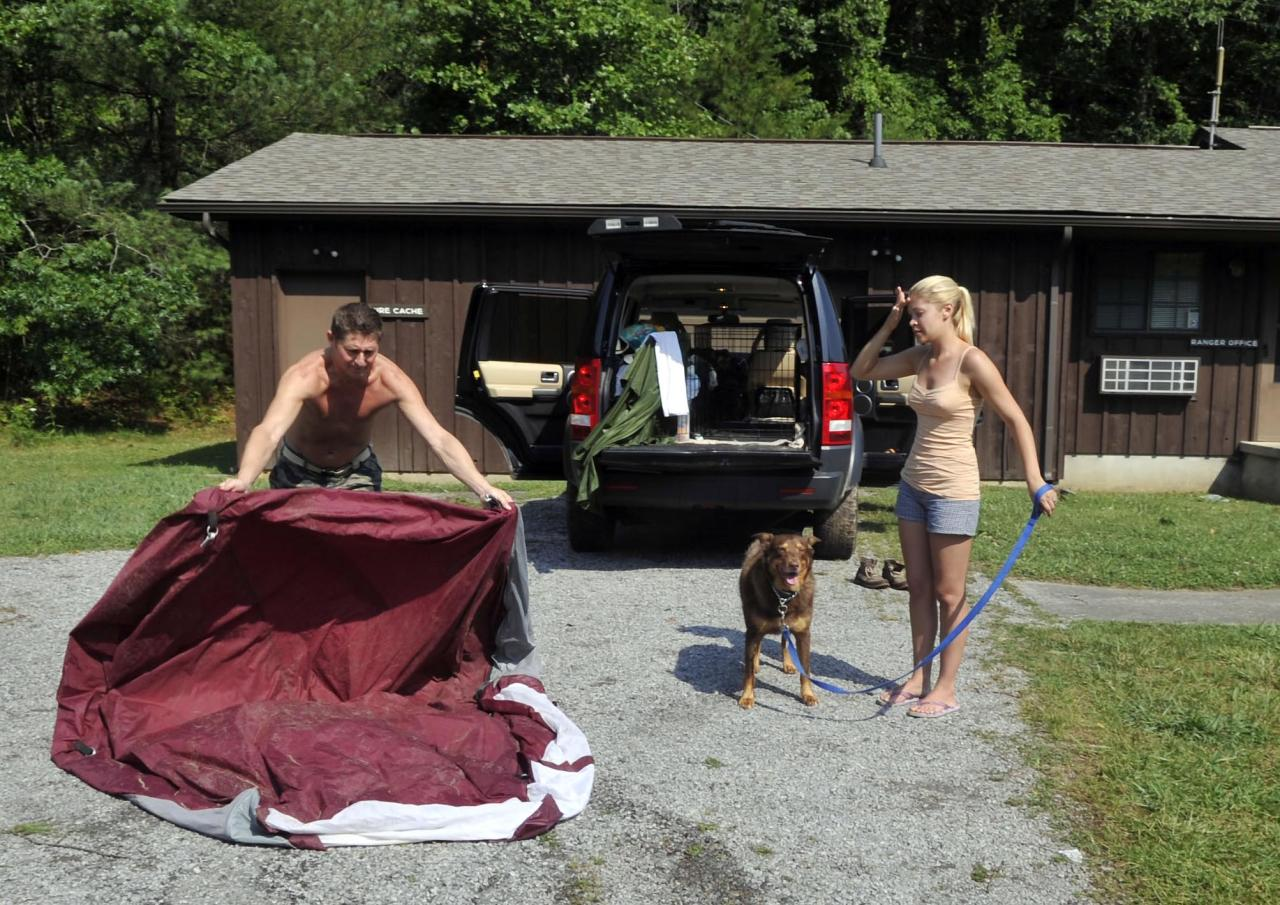 Alex Rudle and his fiancee, Jenna Malone, with their dog, Rocky, pack their camping gear after a fatal storm in the Great Smoky Mountains National Park Friday, July 6, 2012 near Maryville, Tenn. The Chicago couple attempted unsuccessfully to revive Rachael Burkhart, 41, of Corryton, Tenn., after she was struck by a falling tree near Abrams Creek Campground. (AP Photo/The Knoxville News Sentinel, J. Miles Cary)