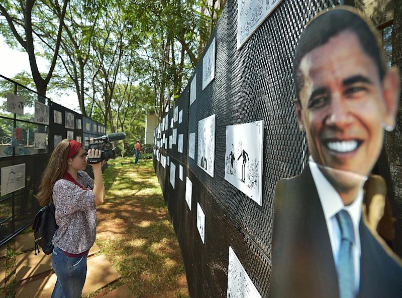 A journalist films at an outdoor exhibition of editorial cartoons and caricatures of US President Barack Obama at PAWA-254 art centre in Nairobi on July 27, 2015 (AFP Photo/Tony Karumba)