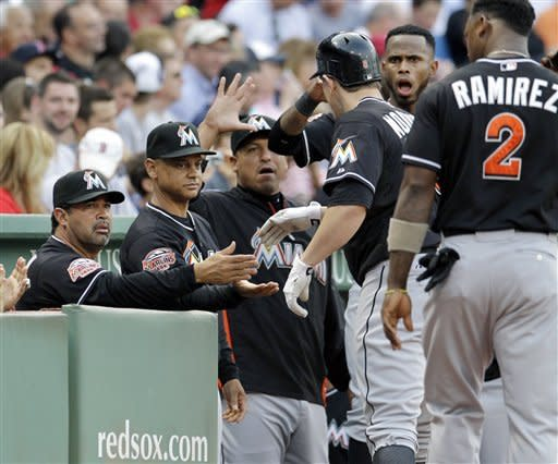 Miami Marlins' Logan Morrison is congratulated at the dugout by manager Ozzie Guillen, far left, and other teammates after Morrison's two-run homer against the Boston Red Sox in the first inning of an interleague baseball game at Fenway Park in Boston on Tuesday, June 19, 2012. (AP Photo/Elise Amendola)