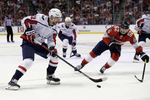 Washington Capitals center Evgeny Kuznetsov, left, skates with the puck as Florida Panthers defenseman MacKenzie Weegar (52) pursues during the second period of an an NHL hockey game, Thursday, Nov. 7, 2019, in Sunrise, Fla. (AP Photo/Lynne Sladky)