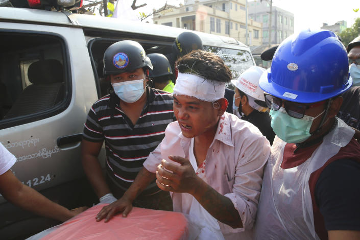 An injured protester is escorted as police tried to disperse a demonstration against the military coup in Mandalay, Myanmar, Friday, Feb. 26, 2021. (AP Photo)