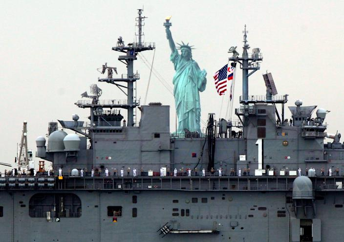 Sailors line the deck of the USS Wasp as she sails by the Statue Of Liberty, in New York, to participate in Fleet Week activities, Wednesday, May 23, 2012. (AP Photo/Richard Drew)