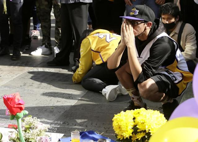 A fan pays his respect as he prays at a memorial for Kobe Bryant at L.A. Live Entertainment Complex, across the street from Staples Center, home of the Los Angeles Lakers in Los Angeles, California, USA, 27 January 2020. EFE/EPA/ALEX GALLARDO