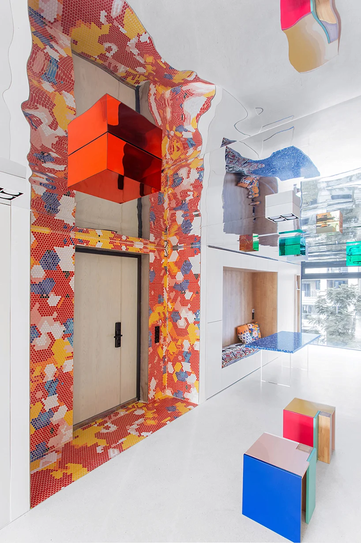 The main entrance to the Chongqing apartment is surrounded by a colorful red, blue, and yellow tile mosaic.