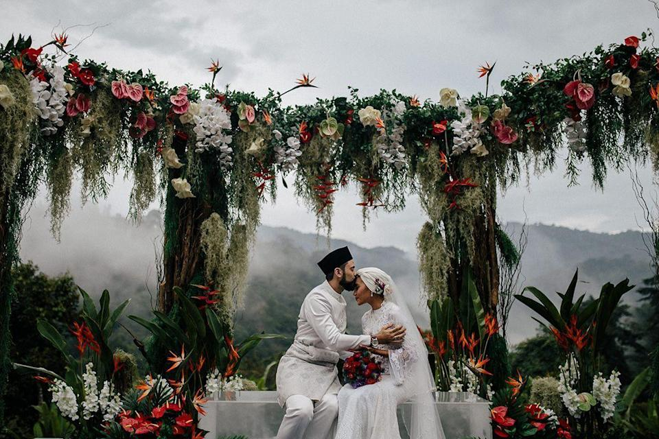 """<p>Whether you're in your backyard or wedding in a remote, far away destination—like the Malaysian jungle pictured here—look to the natural elements of your surroundings when designing your ceremony's focal point. The floral design of this ceremony may be lush and dramatic, but the tropical blooms were sourced locally, using the flora and fauna of the wedding location as a guide. Other than the blooming altar, this couple kept it simple—and let the landscape speak for itself.</p><p><em>Pictured: <a href=""""https://www.harpersbazaar.com/wedding/photos/a28092024/yuna-zarai-adam-sinclair-wedding-malaysia/"""" rel=""""nofollow noopener"""" target=""""_blank"""" data-ylk=""""slk:Yuna and Adam's wedding in Malaysia"""" class=""""link rapid-noclick-resp"""">Yuna and Adam's wedding in Malaysia</a>; Planning and design by <a href=""""https://www.instagram.com/the_calla/?hl=en"""" rel=""""nofollow noopener"""" target=""""_blank"""" data-ylk=""""slk:The Calla"""" class=""""link rapid-noclick-resp"""">The Calla</a> and <a href=""""https://ysaevents.com/"""" rel=""""nofollow noopener"""" target=""""_blank"""" data-ylk=""""slk:YSA Events"""" class=""""link rapid-noclick-resp"""">YSA Events</a>; Florals by <a href=""""https://www.instagram.com/flores.kl/?hl=en"""" rel=""""nofollow noopener"""" target=""""_blank"""" data-ylk=""""slk:FLORES KL"""" class=""""link rapid-noclick-resp"""">FLORES KL</a>.</em></p>"""